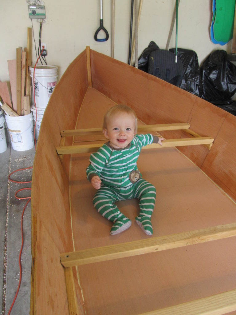 Sam woke up about the time that I had finished gluing the bottom on. So we flipped the boat over and had him try it out.